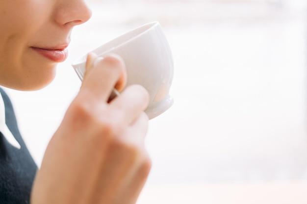 Koffie of thee genot. vrouw genieten van een kopje warme drank. meisje trakteert zichzelf op een heerlijke warme drank