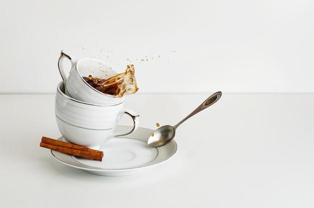 Koffie of thee het bespatten in een porseleinkop op witte achtergrond. kopieer ruimte.