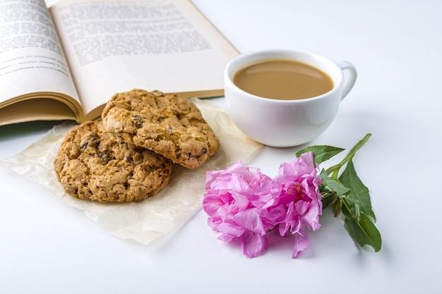 Koffie of thee met melk en haverkoekjes. oud boek en een snack lezen in de lente, zomerdag in de tuin