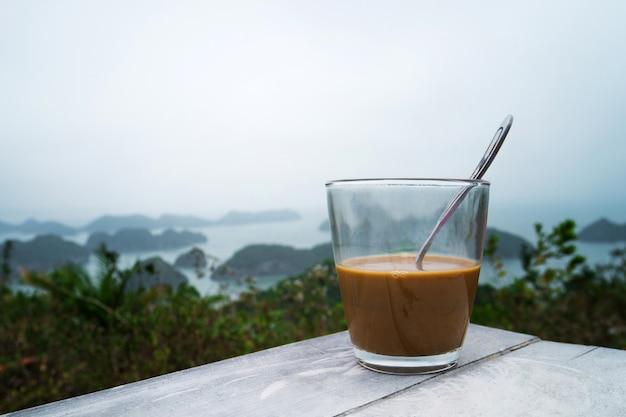 Koffie of thee op tafeleilanden en bergen. traditionele vietnamese koffie in een transparant glas op de achtergrond van een prachtig landschap van halong bay in het noorden van vietnam.