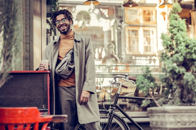 Koffie om mee te nemen. vriendelijke bebaarde man positiviteit uiten terwijl hij tijd in de open lucht doorbrengt