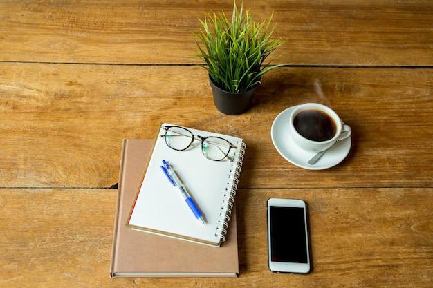 Koffie omhoog en notitieboekje, pen met glazen, mobiele telefoon op houten tafel.