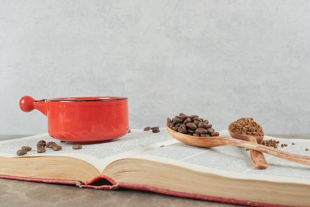Koffie op boek met koffiebonen en gemalen koffie