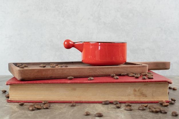 Koffie op een houten bord met koffiebonen en boek