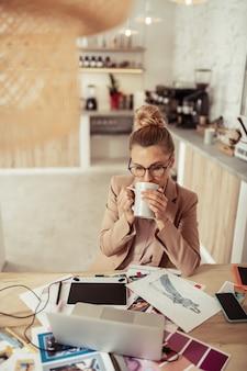 Koffie op het werk. mooie bedachtzame vrouw die haar koffie drinkt en aan haar schetsen werkt.