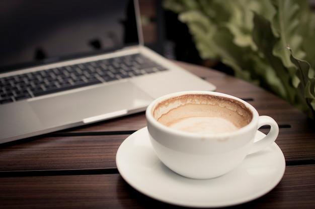 Koffie op tafel met laptop werken in café, ontspannen en vrije tijd concept