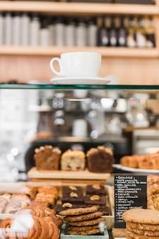 Koffie over glazen kast met gebakken voedsel
