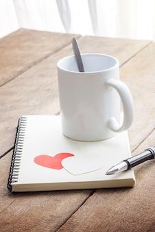Koffie, rood hart, notitieboekje en pen