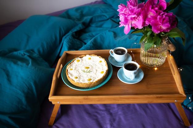 Koffie, roze pioenrozen, cheesecake op een houten dienblad