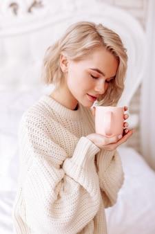 Koffie ruiken. jonge aantrekkelijke vrouw die een beige trui draagt, voelt zich vrolijk ruikende ochtendkoffie