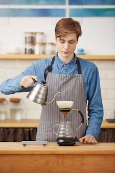 Koffie schenken. leuke barista die koffiedrank voorbereidt, geconcentreerd kijkt.