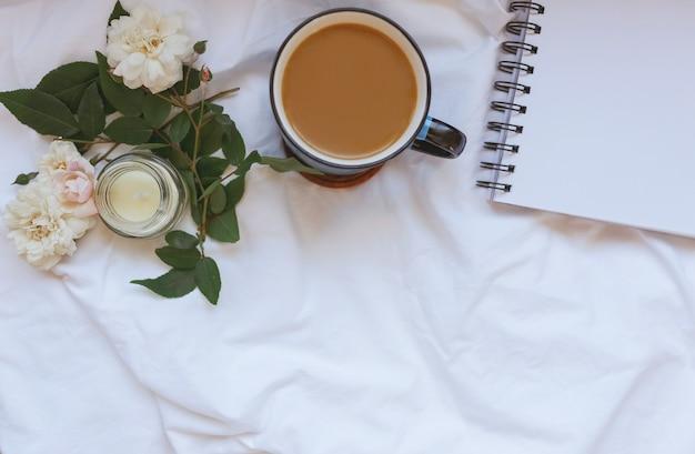 Koffie, schoon notitieboekje. roze bloemen, kaars op witte verfrommelde lakens bovenaanzicht. vrouw thuiswerken. gezellig ontbijt. mock-up. platliggende stijl.
