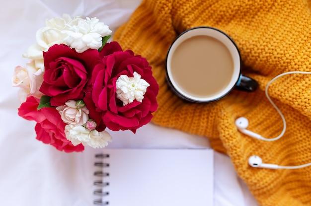 Koffie, schoon notitieboekje. roze bloemen, oordopjes op witte verfrommelde lakens en gele gebreide hoes bovenaanzicht. vrouw thuiswerken. gezellig ontbijt. mock-up. platliggende stijl.