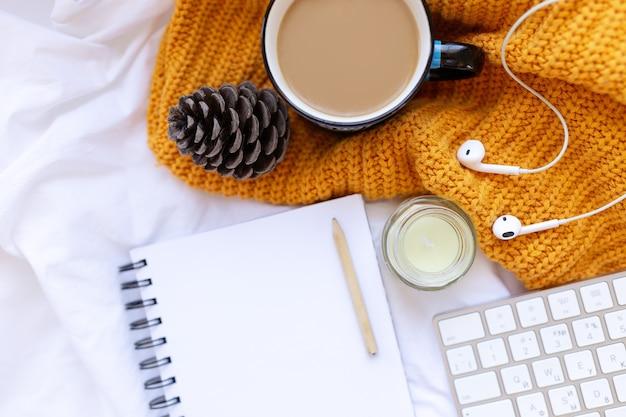 Koffie, schoon notitieboekje. toetsenbord, kegel, kaars, oordoppen op witte verfrommelde lakens en gele gebreide hoes bovenaanzicht. vrouw thuiswerken. gezellig ontbijt. mock-up. platliggende stijl.