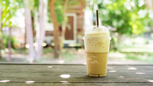 Koffie smoothie op een houten tafel en plant achtergrond.