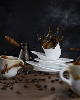 Koffie spatten uit een kopjes op een houten tafel en een zwarte achtergrond.