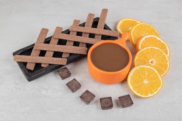 Koffie, stukjes sinaasappel, chocolade en koekjes op marmeren oppervlak