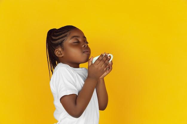 Koffie, thee drinken, genieten met volle teugen. het portret van een klein afrikaans-amerikaans meisje op gele studioachtergrond. vrolijk kind. concept van menselijke emoties, expressie, verkoop, advertentie. kopieerruimte. ziet er schattig uit.
