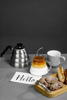 Koffie, theepot met lange tuit, snoep en een kaartje met de inscriptie hallo.