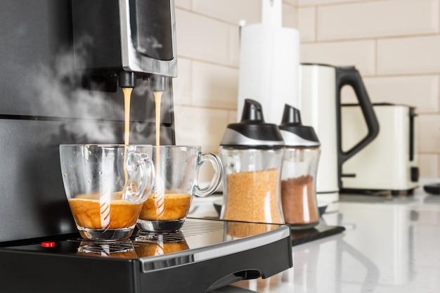 Koffie uit de koffiemachine wordt in glazen bekers gegoten