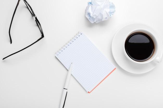 Koffie, vellen papier en verfrommelde proppen op tafel
