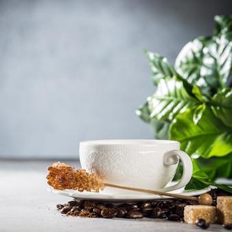 Koffie vers gezet in een witte kop met bonen en bladeren. voedseloppervlakte met exemplaarruimte