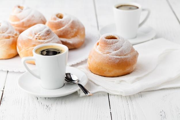 Koffie witte kop, croissants op donkere retro tafel, selectieve aandacht. ontbijt concept