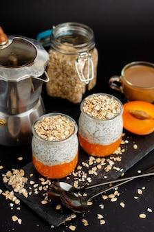 Koffie, yoghurtchia pudding met verse abrikozen en havervlokken voor het ontbijt op zwart