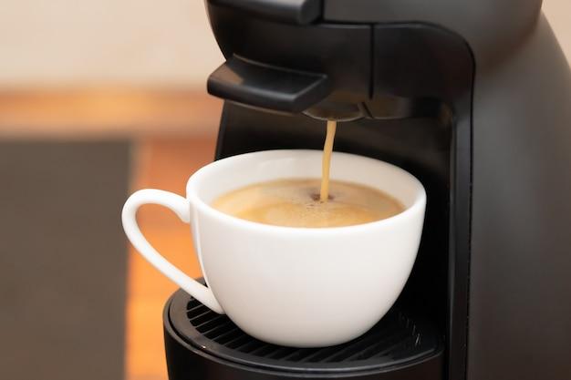 Koffie zetten in een capsulemachine. geurige warme drank wordt in een kopje gegoten. echt lekker zelfgemaakt.
