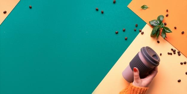 Koffie zonder afval. eco-vriendelijke herbruikbare koffiekopjes in handen, geometrisch bovenaanzicht op gesplitst papier in groene, gele en oranje kleurtinten. panoramisch bannerontwerp met exemplaarruimte.
