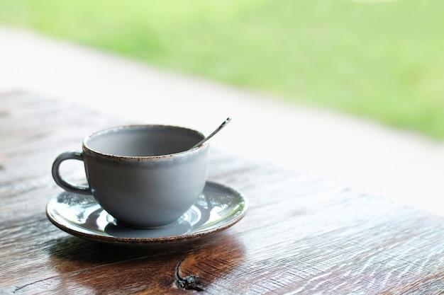 Koffieamericano of espresso in lichtblauwe kop op houten lijst in straatkoffie met exemplaarruimte