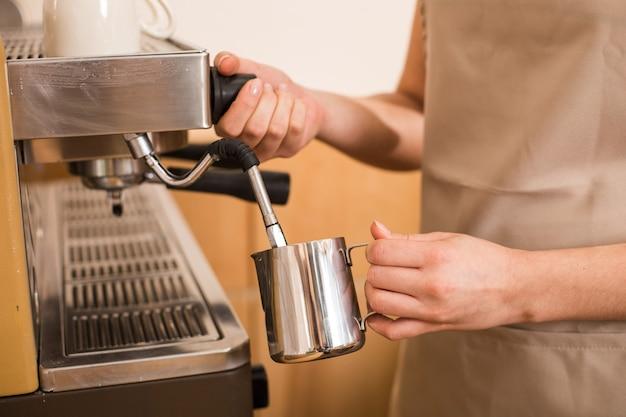 Koffiebereiding. close-up van een kopje dat wordt gebruikt voor de bereiding van koffie door een aardige positieve aangename vrouw