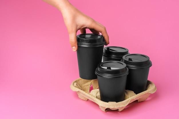Koffiebezorging. menselijke hand met afhaalmaaltijden koffiekopje op papier achtergrond