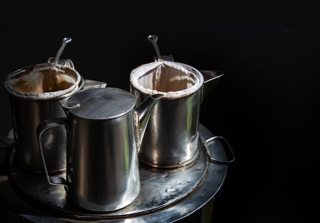 Koffieboiler in vintage thaise traditionele mand op metaal