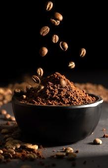 Koffiebonen die in een zwarte kom vallen