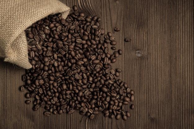 Koffiebonen die van een rieten zak tegen een houten achtergrond uitvallen.