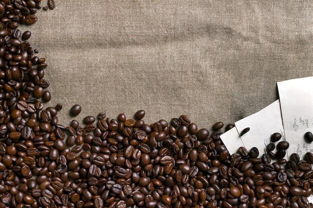 Koffiebonen en bladmuziek op juteachtergrond