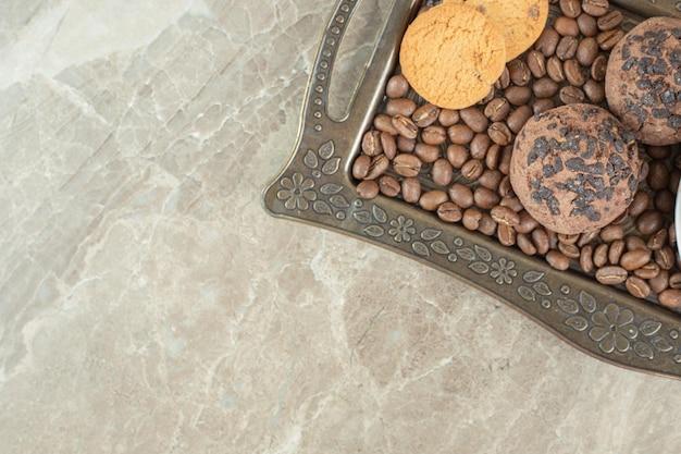 Koffiebonen en koekjes op donkere plaat