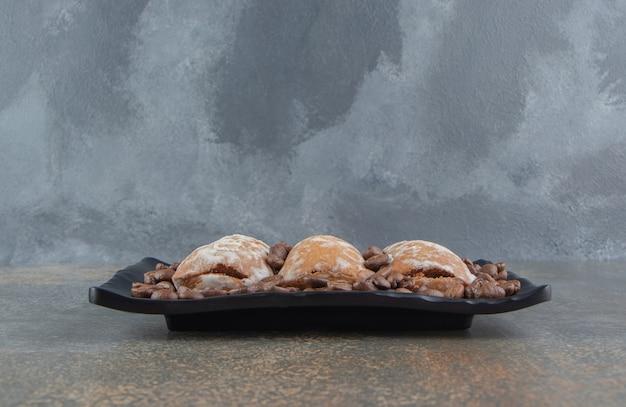 Koffiebonen en koekjes op een zwarte schotel