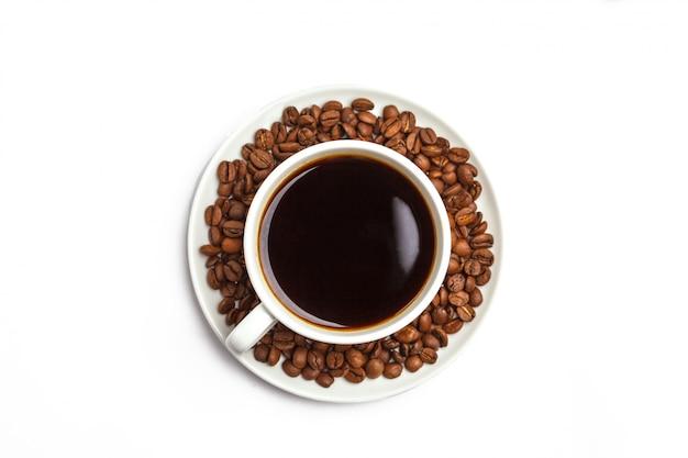 Koffiebonen en koffie in een witte kop die op wit wordt geïsoleerd. bovenaanzicht, kopieer ruimte