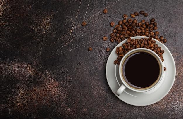 Koffiebonen en koffie in een witte kop op een donkere roestige achtergrond. bovenaanzicht, kopieer ruimte