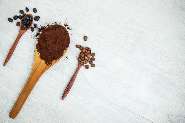 Koffiebonen en koffiepoeder op houten lepels