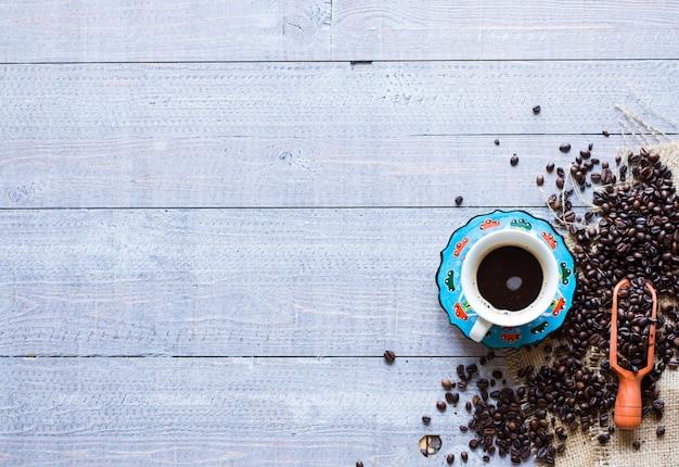 Koffiebonen en kopje koffie met andere componenten op verschillende houten achtergrond. vrije ruimte voor tekst