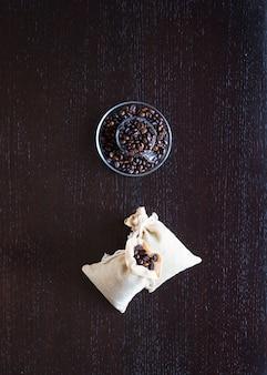 Koffiebonen en kopje koffie met andere componenten op verschillende houten achtergrond.