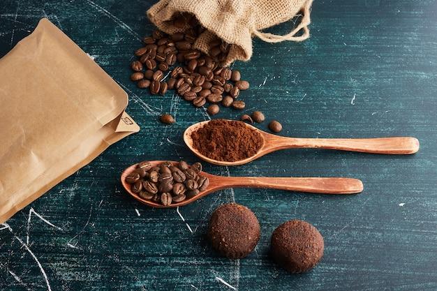 Koffiebonen en poeder in houten lepels.