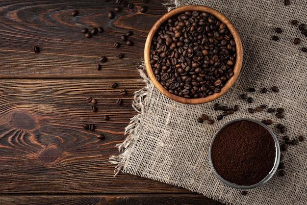 Koffiebonen en poeder op donkere houten achtergrond.
