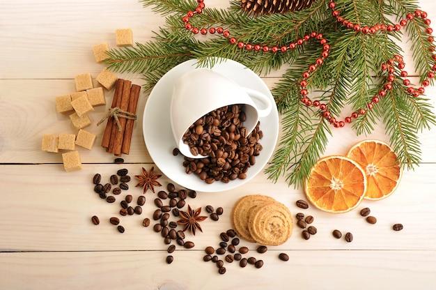 Koffiebonen gegoten in een mok op de kerstachtergrond van suiker, boomtakken, kaneel en anijs