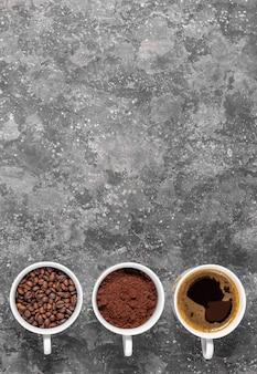 Koffiebonen, gemalen koffie en espresso in koppen copyspace