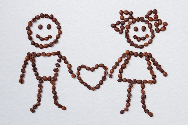 Koffiebonen gerangschikt in verliefde paar met hart. liefde en koffie concept. geïsoleerd op wit.