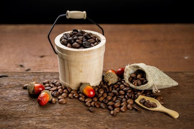 Koffiebonen gevuld in houten emmer, sommige liggen op tafel en in een stoffen zak. decoratie met gedroogd eiken fruit.